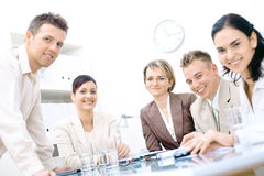Staff meeting. Five business colleagues sitting around table and working together, looking at camera, smiling royalty free stock photo