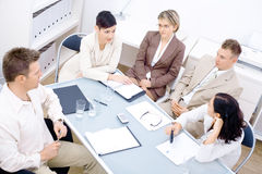 Staff meeting. Five business colleagues sitting around table and having a meeting stock photos