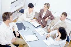 Staff meeting. Five businesspeople sitting around table in office and having a meeting. Discussing business plans and writing notes on paper royalty free stock photo