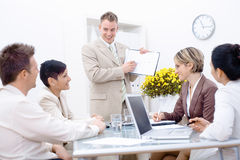 Staff meeting at office. Young business people having a business meeting, sitting around table at office, businessman showing diagram stock photos