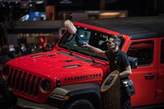 Staff member cleaning red Jeep, Rubicon model. stock images