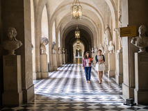 Staff members walk down Versailles Palace corridor, France. Royalty Free Stock Photography