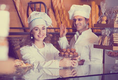 Staff offering fancy and sponge cakes. Cafe people offering fancy and sponge cakes for sale Stock Photo