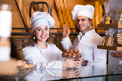 Staff offering fancy and sponge cakes. Cafe people offering fancy and sponge cakes for sale Stock Image