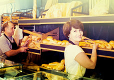 Staff offering fresh baguettes and buns in bakery Stock Photography