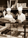 Staff offering fresh baguettes and buns in bakery. American  staff offering fresh baguettes and buns in bakery Royalty Free Stock Photo