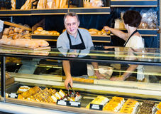 Staff offering fresh baguettes and buns in bakery Stock Photo