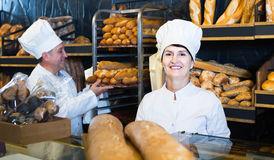 Staff offering fresh baguettes and buns in bakery. Positive russian staff offering fresh baguettes and buns in bakery Royalty Free Stock Image