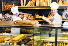 Staff offering fresh baguettes and buns in bakery. Russian staff offering fresh baguettes and buns in bakery Stock Image