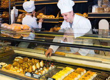 Staff offering fresh baguettes and buns in bakery Royalty Free Stock Photos
