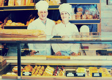Staff offering fresh baguettes and buns in bakery Stock Images