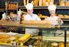 Staff offering fresh baguettes and buns in bakery. Spanish staff offering fresh baguettes and buns in bakery Stock Photography