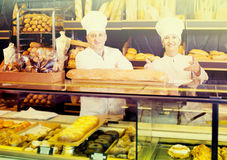 Staff offering fresh baguettes and buns in bakery. Spanish staff offering fresh baguettes and buns in bakery Royalty Free Stock Images