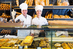 Staff offering fresh baguettes. Happy employees offering fresh baguettes and buns in bakery Stock Image