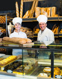 Staff offering fresh baguettes. Happy people offering fresh baguettes and buns in bakery Stock Photos