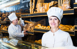 Staff offering fresh baguettes. Happy person offering fresh baguettes and buns in bakery Royalty Free Stock Photo