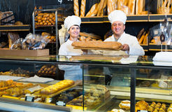 Staff offering fresh baguettes. Mature staff offering fresh baguettes and buns in bakery Royalty Free Stock Photography