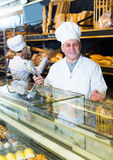 Staff offering fresh baguettes. Mature male staff offering fresh pastry in sweet-shop Stock Photography