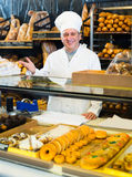 Staff offering fresh pastry. Russian male staff offering fresh pastry in sweet-shop Royalty Free Stock Photography