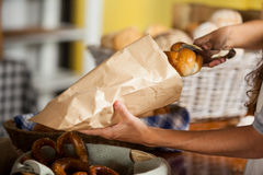 Staff packing bread in paper bag at bakery shop Stock Image