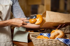 Staff packing bread in paper bag at bakery shop Stock Photography