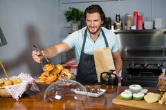 Staff packing a croissant in paper bag at counter. In coffee shop Stock Photography