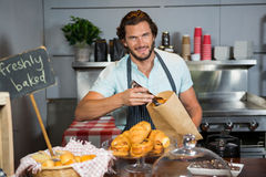 Staff packing a croissant in paper bag at counter Stock Photography