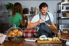 Staff packing a cup cake in paper bag at counter. In coffee shop Stock Image