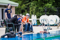 Staff People on the Side of the Pool Checking Performance and Ju Royalty Free Stock Photo