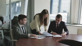 The staff of the publishing agency at work. A business team consisting of two attractive men and a beautiful girl. Work with documents. Discussion of projects stock video footage