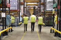 Staff in reflective vests walking from camera in a warehouse royalty free stock images