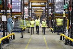 Staff in reflective vests walking to camera in a warehouse stock photography