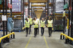 Staff in reflective vests walking to camera in a warehouse royalty free stock image