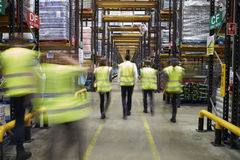 Staff in reflective vests walking in a warehouse, back view Stock Photo