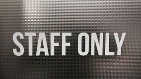 A STAFF ONLY sign on a metallic background. A sign in a hub office for tech workers lets workers know that this room is for `STAFF ONLY Stock Photo