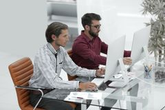 Two employees , sitting in front of computer. It staff. Two employees , sitting in front of computer monitors Stock Photography