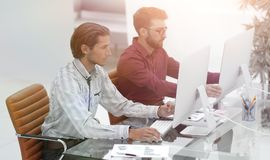 Two employees , sitting in front of computer. It staff. Two employees , sitting in front of computer monitors Royalty Free Stock Image