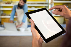 Staff using digital tablet at bakery counter Stock Images