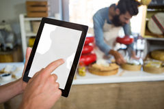 Staff using digital tablet at bakery counter. In market Royalty Free Stock Photos