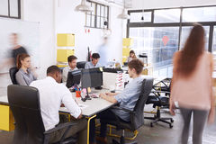 Staff walking through a busy open plan office Stock Images