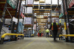 Staff in a warehouse move between storage racks, motion blur Royalty Free Stock Photo