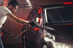 Car wash and coating business with ceramic coating.Spraying varnish to car. Staff wear protective mask and eyewear at work.Car Care Business. Automobile royalty free stock images