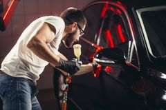 Car wash and coating business with ceramic coating.Spraying varnish to car. Staff wear protective mask and eyewear at work.Car Care Business. Automobile royalty free stock image