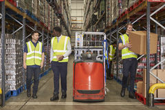 Staff at work in the aisle of a busy distribution warehouse stock image