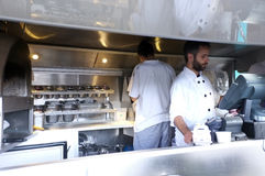 Staff work on a pizza vendor. Staff work in a mobile pizza vendor in South Bank, London royalty free stock image