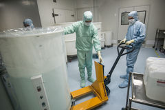 Staff working in clean area in the production site of the biotechnology company. ST. PETERSBURG, RUSSIA - NOVEMBER 16, 2016: Staff working in clean area in the stock photography