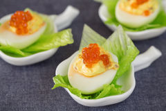 Staffed egg appetizer with red caviar garnish Stock Photo