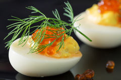 Staffed eggs with red caviar garnish and dill decoration Stock Photo