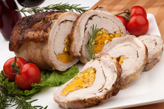 Staffed Pork Loin Roulade. Dried apricots, pistachios, and rosemary staffed pork loin roulade served with salad, tomatoes and glass of red wine Stock Images