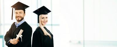 Staffelung - glückliche Studenten, die Kleid und Kappe tragen stockbild